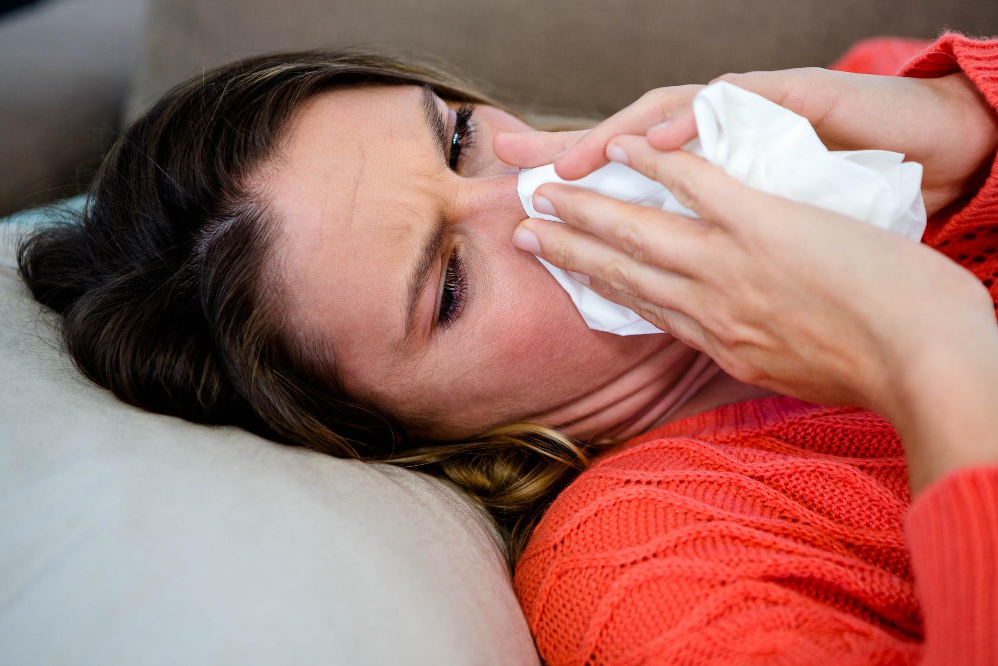 Frau liegend putzt sich die Nase